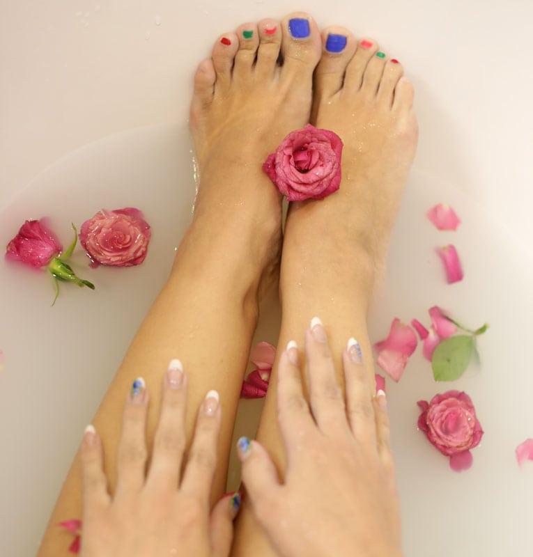 Füsse und Hände in Badewanne mit Rosen