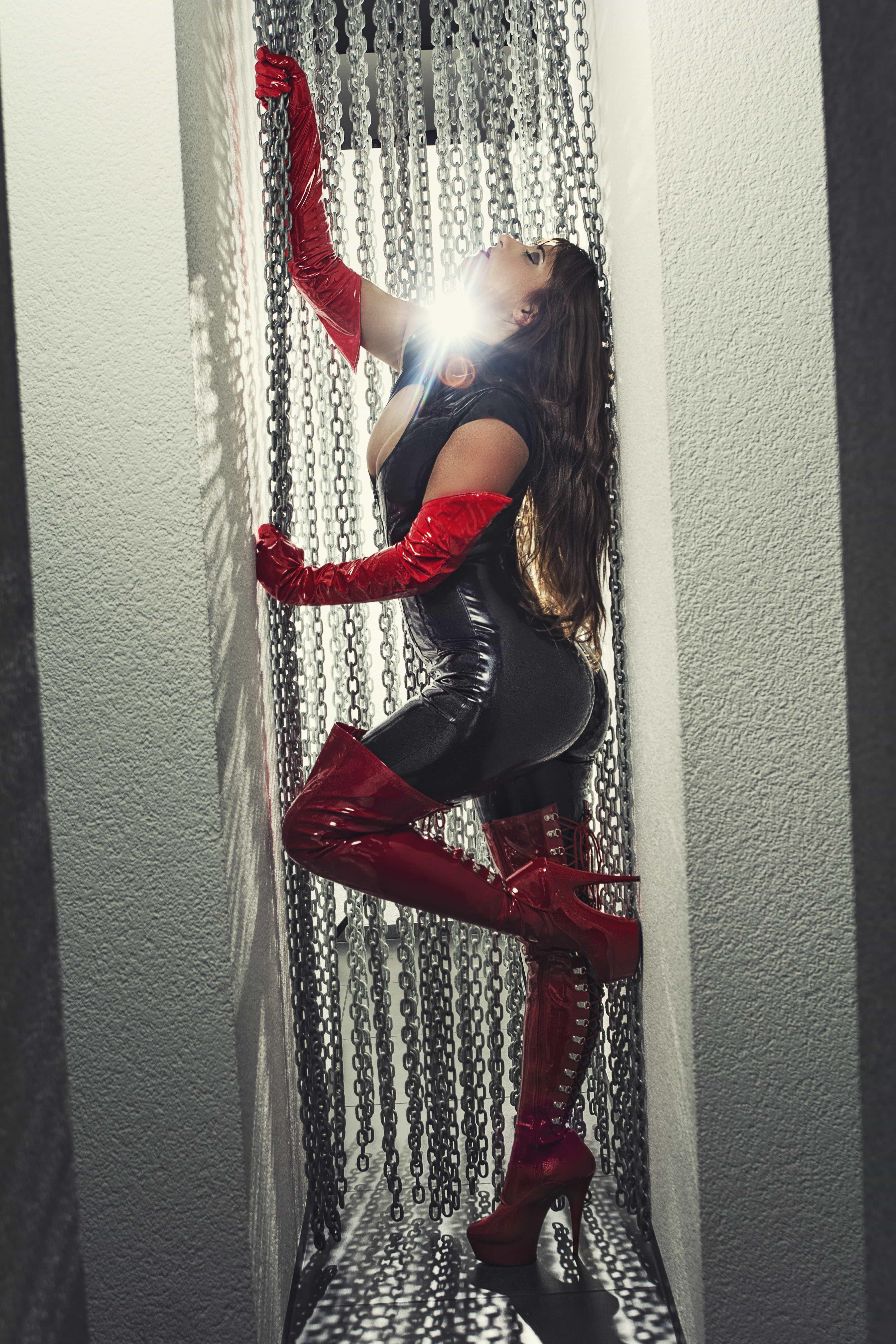 Domina im Gegenlicht mit Ketten und Latex rot schwarz
