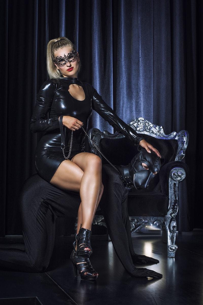 Domina sitzt auf Sklavenhund