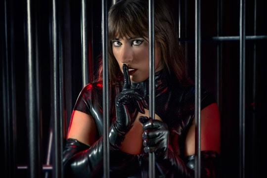 Domina vor Käfig